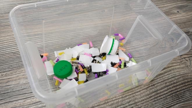 Собранные в одной емкости кусочки пластика и металла